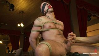 pretty guy tied on a chair, blindfolded and ball gagged