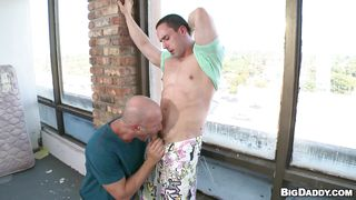 bald dude sucking a muscled guy's cock