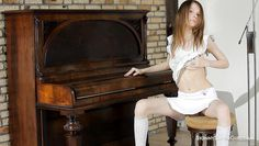 skinny girl at the piano behaves naughty