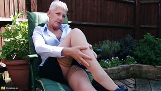 mature european lady relaxes sexily in the backyard