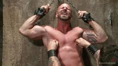 muscled man chained and sexually dominated