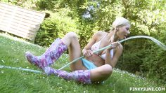blondie plays with the hose in her garden