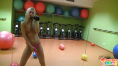 playing with the balls and a fake cock in the gym