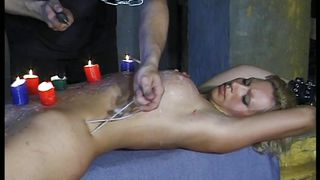slave gets candle wax poured on her